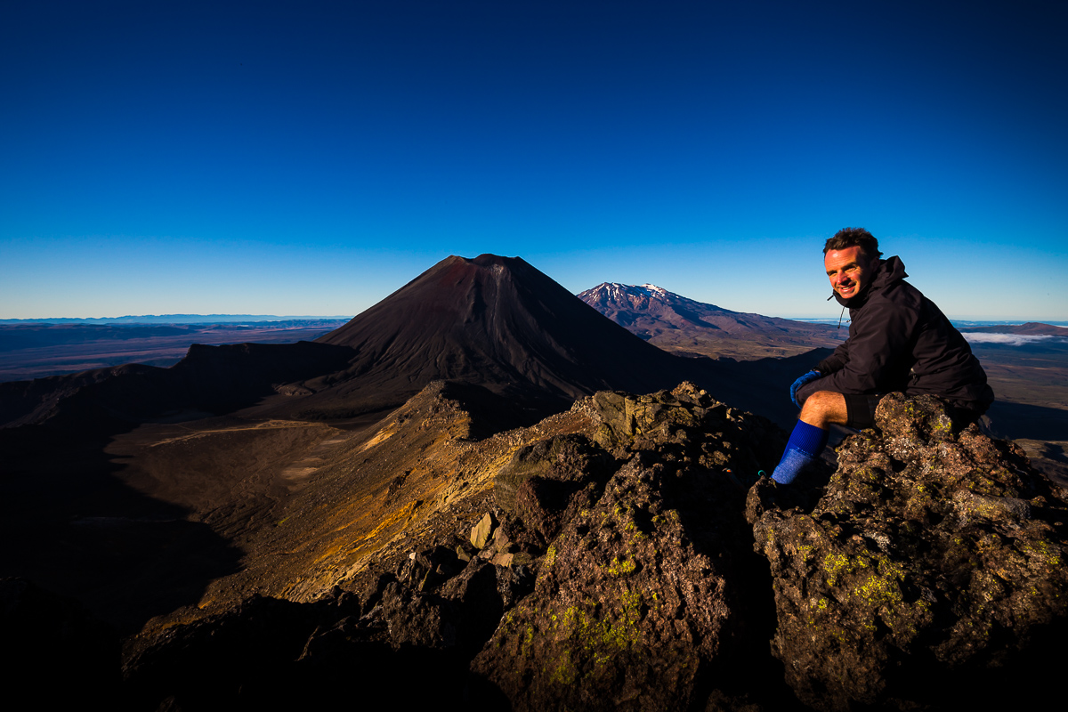 Photographer Adam Firth looking over the Tongariro crossing from Mount Tongariro summit