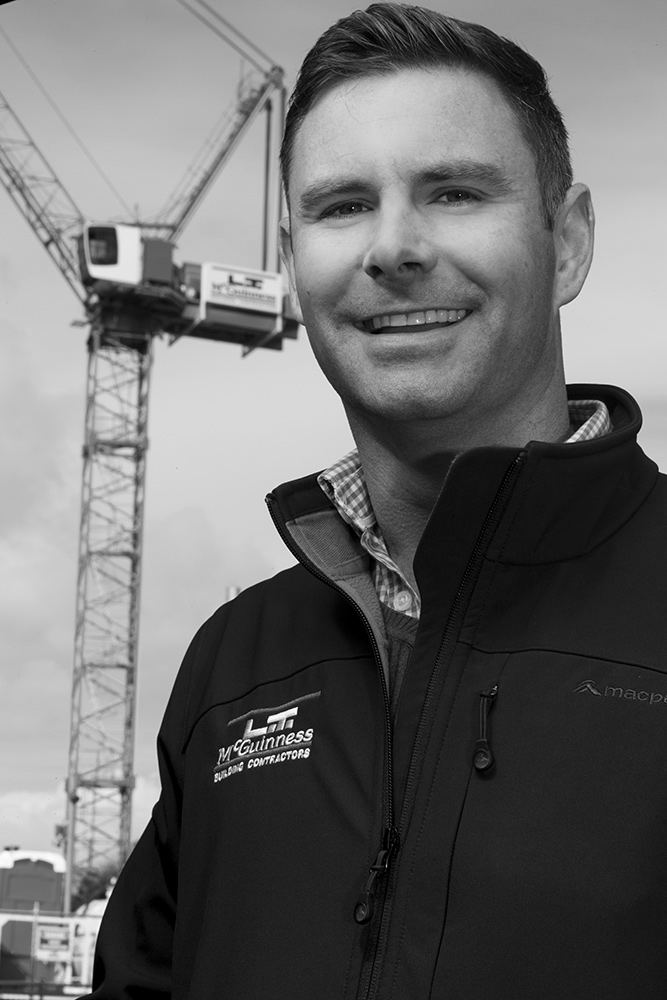 construction staff portraits bw with crane in background