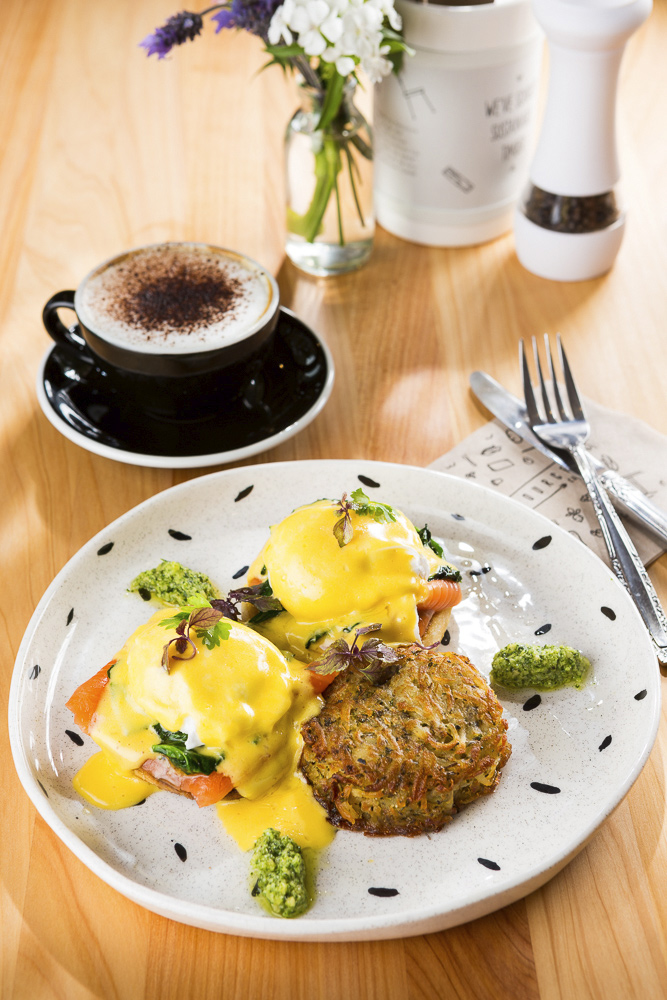 Cafe food photography image of Salmon and poached eggs benedict with potato courgette rosti