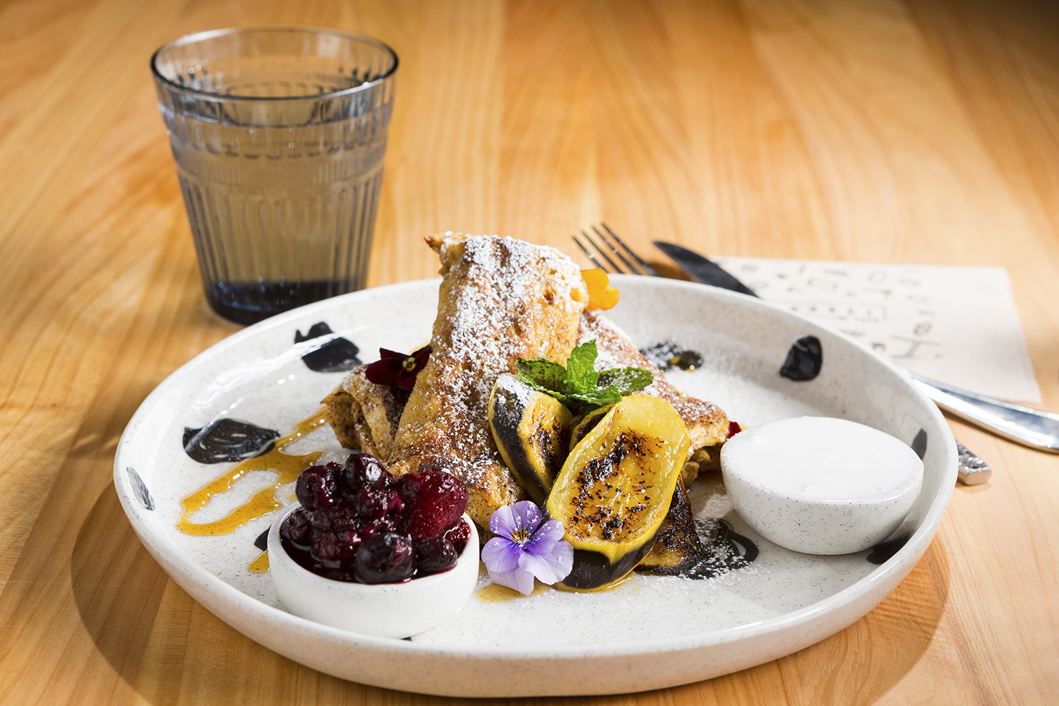 Photography of french toast with grilled banana, coconut yoghurt, maple syrup and berry compote