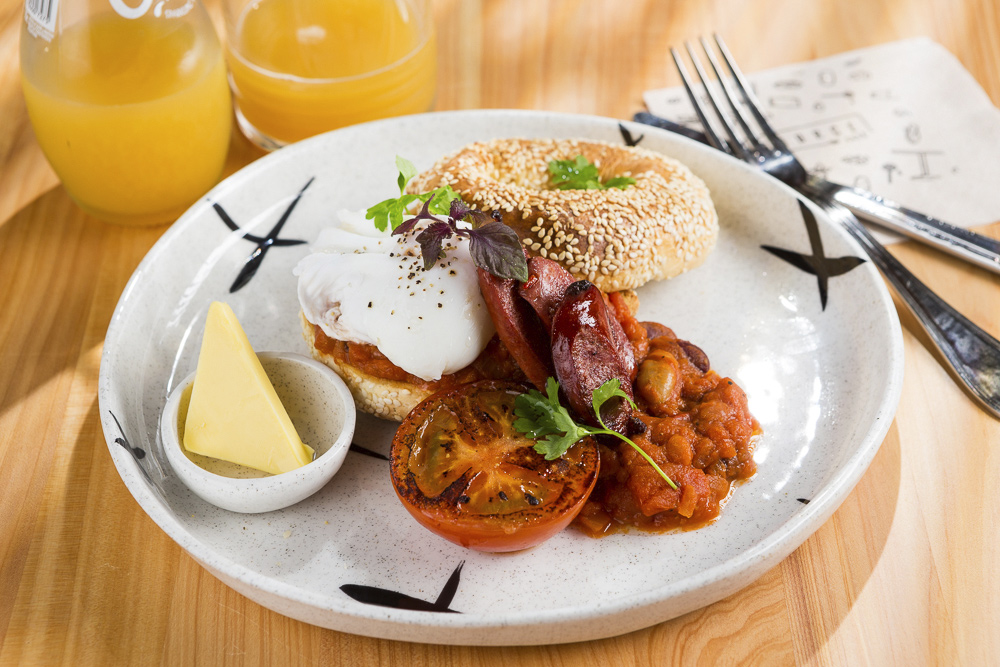 Side on photo of a beans, chorizo, and poached egg bagel taken for cafe food photography shoot for source cafe