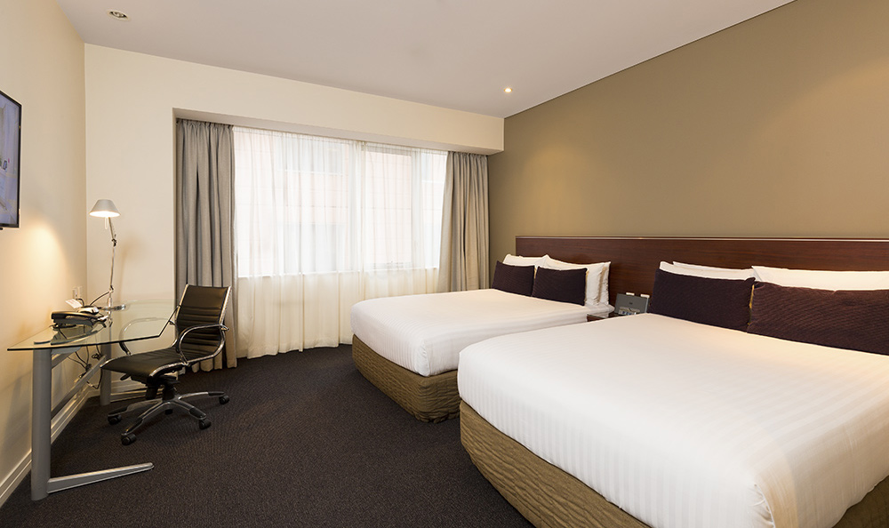 hotel room photography of warm toned room with two double beds